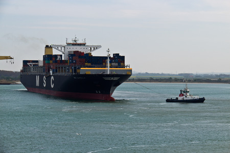 tugboat: DUNKIRKFRANCE - April 17, 2014: Tugboat towing the MSC Capella container ship in the Dunkirk harbor. Editorial