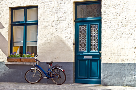 quaint: Quaint home with blue door and blue window matching blue bike