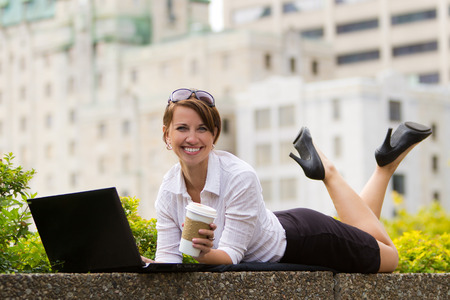 casualy: Young business woman casualy works on laptop in the city