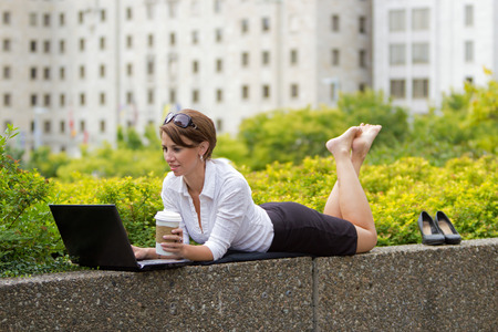 casualy: Young business woman kicks off her shoes and casualy works on laptop in the city