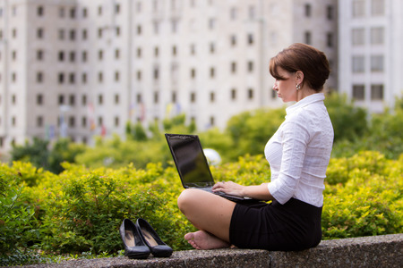 casualy: Young business woman kicks off her shoes and casualy works in the city Stock Photo