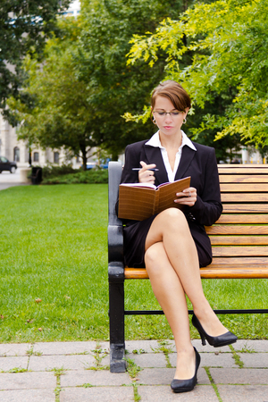 siting: Stylish business woman siting on park bench writing in notebook Stock Photo