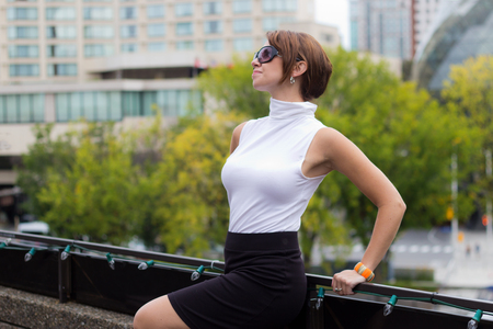 sex appeal: Sexy, sofisticated woman with sunglasses poses in urban city area Stock Photo