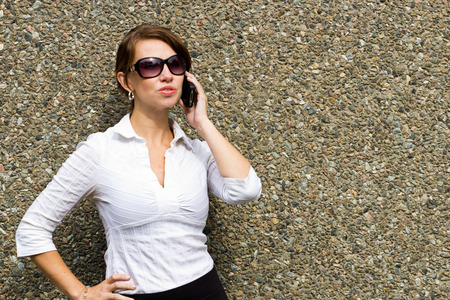 sofisticated: Sofisticated woman with sunglasses using mobile smart phone Stock Photo
