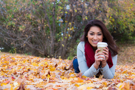 lying on leaves: Fashionable woman with coffee lying down on autumn leaves