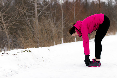 hamstrings: Sporty fit woman stretches her hamstrings before running on trail on cold winter day. Wellness workout and healthy lifestyle concept.