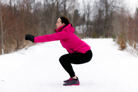 girl squatting: Fit woman doing squats exercises on outdoor winter nature trail.  Wellness workout and healthy lifestyle concept