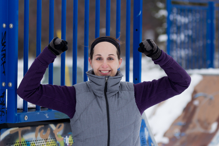 grafiti: Fit attractive sporty woman outdoors on cold winter day flexing biceps. Fit healthy lifestyle concept