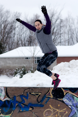 grafiti: Fit sporty woman outdoors in winter running gear at urban park with graffiti jumps with arms up. Fit healthy lifestyle concept.