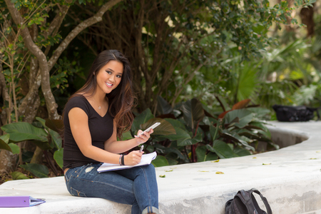 Smiling female asian student sitting outside writing in notebook journal checks her text message on smart phone Stock Photo