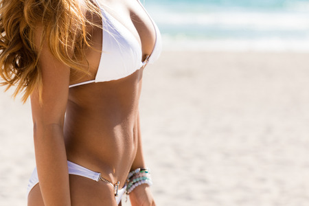 Woman with beautiful body on a tropical beach. Close-up of bikini abs. Banque d'images