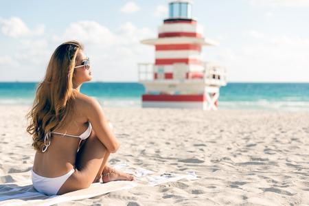 Woman in bikini sitting on the beach with lifeguard tower in background