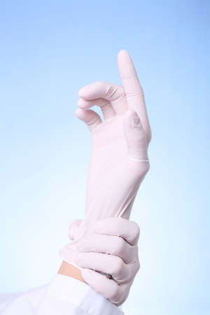 proctologist: Female doctor putting on latex gloves for medical examination