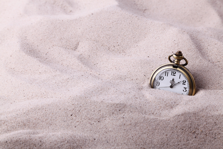 Vintage pocket watch partially buried in the sand
