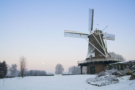 Winter scene with mill after sunset photo