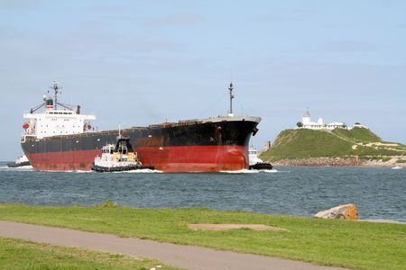 escorted: Cargo ship being escorted to the Newcastle harbour, Australia
