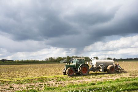 Farmer fertilizing the land by tractor photo