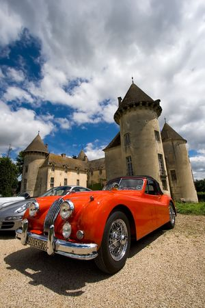 BEAUNE, FRANCE - JUNE 12: Red classic sportscar in front of the Savigny castle. Savigny Castle Museum. June 12, 2010 in Beaune, France