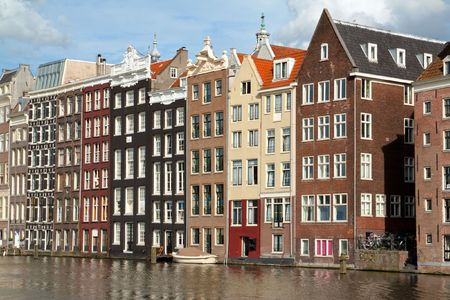 Old 17th and 18th century brick houses along a canal in Amsterdam, Holland. Stock Photo - 7671346