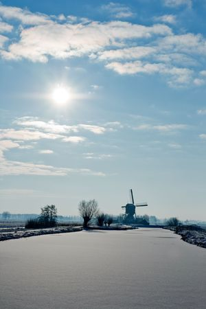 Frozen river and Dutch windmill on a cold winterday Stock Photo - 7761526
