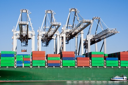 Large harbor cranes loading a container ship