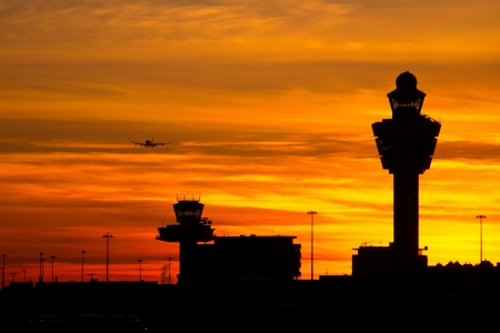 tourism industry: Plane arriving at Amsterdam-Schiphol airport during sunset  Stock Photo