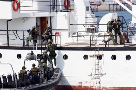 anti piracy: DEN HELDER, THE NETHERLANDS - JULY 7: Dutch Marines entering a ship during an anti piracy demonstrion at the Dutch Navy Days on July 7, 2012 in Den Helder, The Netherlands