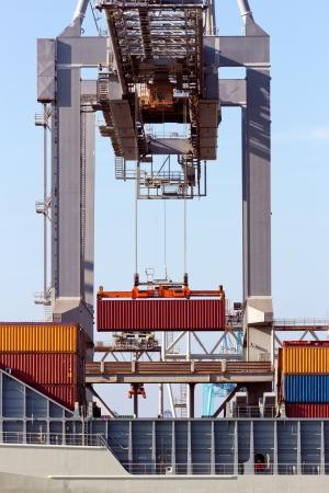 camion grua: Grúa del puerto levanta un gran contenedor marítimo Foto de archivo