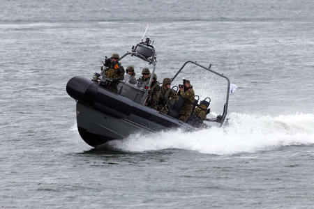 DEN HELDER, THE NETHERLANDS - JUNE 23: Dutch Marines in a speedboat during an assault demo at the Dutch Navy Days on June 23, 2013 in Den Helder, The Netherlands
