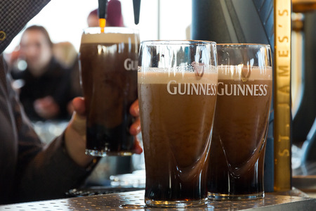 DUBLIN, IRELAND - FEB 15, 2014: Pints of beer are served at The Guinness Brewery on Feb 15, 2014. The brewery where 2.5 million pints of stout are brewed daily was founded by Arthur Guinness in 1759. Editorial