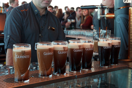 DUBLIN, IRELAND - FEB 15, 2014: Pints of beer are served at the popular Guinness Brewery on Feb 15, 2014. The brewery where 2.5 million pints of stout are brewed daily was founded by Arthur Guinness in 1759.