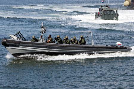anti piracy: DEN HELDER, THE NETHERLANDS - JULY 7: Dutch Swat team in a speedboat during an assault demo at the Dutch Navy Days on July 7, 2012 in Den Helder, The Netherlands