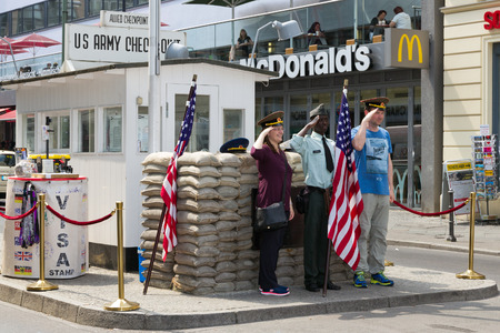 mauer: BERLIN, GERMANY - MAY 23: Tourists posing at the former Allied checkpoint Charlie on May 23, 2014. Nowadays this site is a tourist attraction.  Editorial