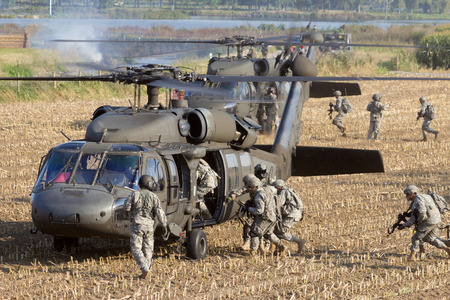 Soldiers of the 82nd Airborne Division enter a Black Hawk helicopter.