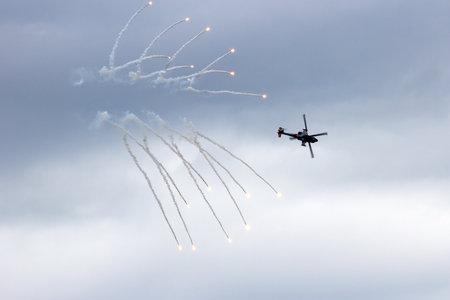 looping: GILZE-RIJEN, NETHERLANDS - JUNE 21:Dutch Air Force AH-64 Apache in a looping firing off flares at the Royal Netherlands Air Force Days June 21, 2014 in Gilze-Rijen, Netherlands.