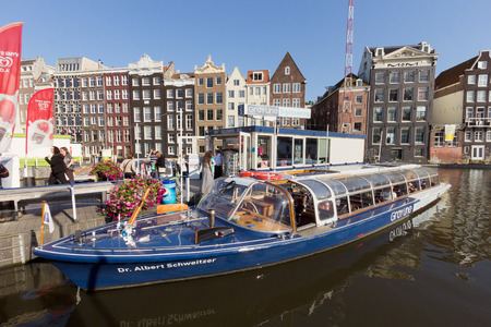 watery: AMSTERDAM, NETHERLANDS - AUG 27 : Canal boat in front of typical Amsterdam canal houses on Aug 27, 2014. Amsterdam is the worlds most watery city. It has more than one hundred kilometres of canals.