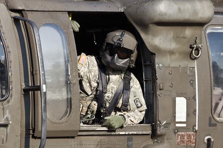 blackhawk helicopter: GRAVE, NETHERLANDS - SEP 17: Crewchief looking out of a Blackhawk helicopter during the Operation Market Garden memorial on Sep 17, 2014 Grave, Netherlands. Market Garden was a large Allied operation in 1944. Editorial