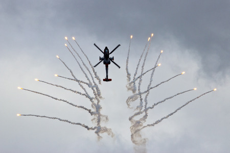 looping: GILZE-RIJEN, NETHERLANDS - JUNE 20:Dutch Air Force AH-64 Apache in a looping firing off flares at the Royal Netherlands Air Force Days June 20, 2014 in Gilze-Rijen, Netherlands.