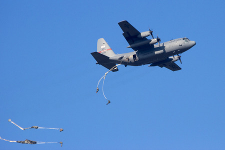 GROESBEEK, NETHERLANDS - SEP 18: A USAF C-130 Hercules is dropping paratroopers from the 82nd Airborne Division at the Operation Market Garden memorial. Market Garden was a large Allied operation in 1944