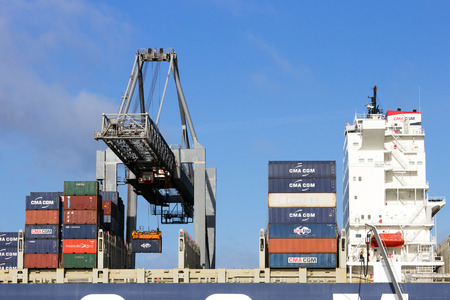 rotterdam: ROTTERDAM, THE NETHERLANDS - JAN 13, 2012: Gantry crane operator placing a container in a cargo ship the Port of Rotterdam. The port is the Europ Editorial