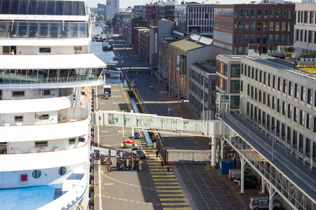 accommodate: AMSTERDAM - SEP 2, 2014: A cruise ship is docked at Passenger Terminal Amsterdam (PTA). The terminal is in use since 2000 and is 600 meters long to accommodate large cruise ships.