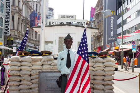 allied: BERLIN, GERMANY - MAY 23: Man dressed as a US Army soldier stands with an American flag at the former Allied checkpoint