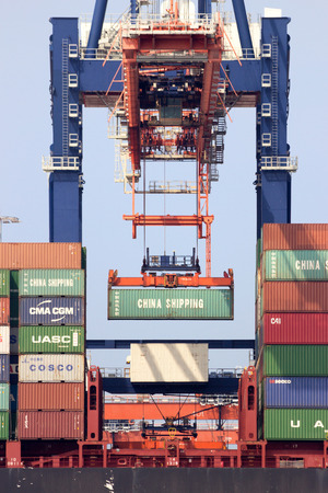 rotterdam: ROTTERDAM, THE NETHERLANDS - AUG 1, 2014: Gantry crane operator placing a container in a cargo ship the Port of Rotterdam. The port is the Europ Editorial