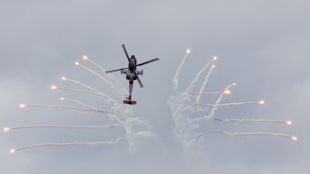 looping: GILZE-RIJEN, NETHERLANDS - JUNE 21, 2014: Royal Netherlands Air Force AH-64 Apache attack helicopter in a looping firing off flares at the Royal Netherlands Air Force Days. Editorial