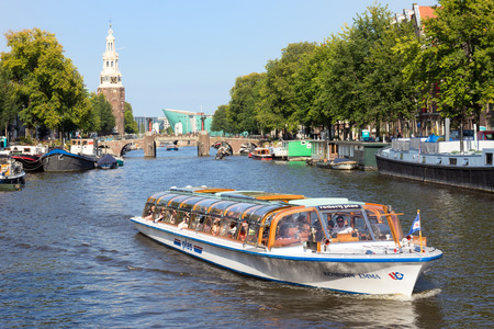 watery: AMSTERDAM, NETHERLANDS - AUG 27, 2014: Canal boat in one of the canals in Amsterdam. The city is the worlds most watery city. It has more than one hundred kilometres of canals.