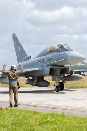 jetplane: WITTMUND, GERMANY- JUNE 29: Ground crew member guiding a newly arrived Eurofighter Typhoon which has officially replaced the F-4 Phantom on the Phantom Pharewell Day.