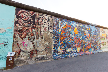 largest: BERLIN - MAY 21: Fragment of the East Side Gallery on May 21,2014 in Berlin. Its a 1.3 km long part of original Berlin Wall which collapsed in 1989 and now is the largest world graffiti gallery Editorial