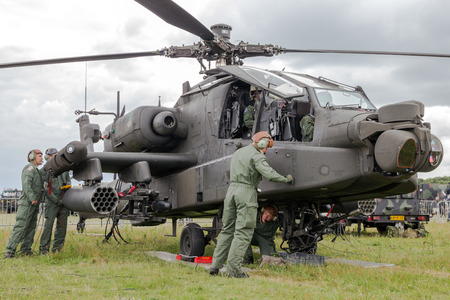 military aircraft: GILZE-RIJEN, NETHERLANDS - JUNE 20, 2014: Ground crew preparing a AH-64 Apache attack helicopter at the Royal Netherlands Air Force Days .