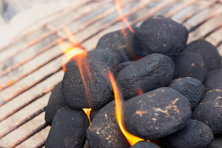 briquettes: Charcoal briquettes on fire in a BBQ Stock Photo