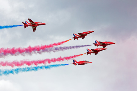 acrobatic: VOLKEL, NETHERLANDS - JUNE 15, 2013: RAF airshow demonstration team Red Arrows performing at the Dutch Air Force Open Days. The Red Arrows have performed over 4,600 displays in 56 countries worldwide.
